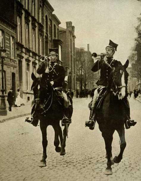 """Lanciers belges parcourant les rues de la ville en sonnant de la trompette. """"Chaque matin à travers les villes belges, des landiers, tels les hérauts d'armes du temps jadis, on fait,  au milieu des acclamations du peuple ému, l'appel des hommes valides. Simplement et sans forfanterie, les volontaires s'engagent en masse pour combattre, aux côtés des troupes alliées, les """"Barbares"""" qui se livrent à des actes de brutalité inouïe. La Belgique a frémi d'indignation. Elle palpite de foi patriotique et son élan irrésistible la place au premier rang dans l'histoire contemporaine."""